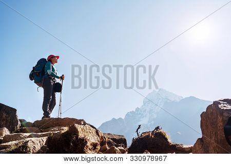 Young Hiker Backpacker Female On Cliff Edge Enjoying The Thamserku 6608m Mountain During High Altitu