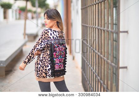 Young beautiful girl wearing animal print cardigan standing on backview the wall at the town street