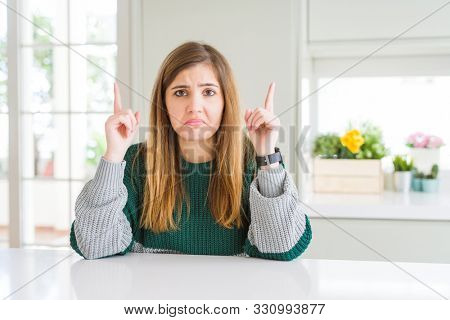 Young beautiful plus size woman wearing casual striped sweater Pointing up looking sad and upset, indicating direction with fingers, unhappy and depressed.