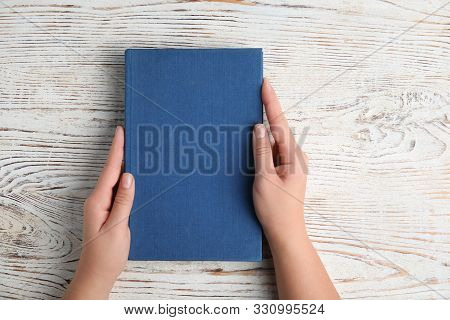 Woman Holding Hardcover Book On White Wooden Background, Top View