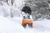 Man using a snowblower to clear his sidewalk and driveway poster