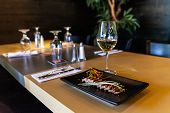 A closeup view of tuna tataki, a briefly seared fish dish marinated in vinegar, served with white wine on a bistro table, with blurry glasses and tableware. poster