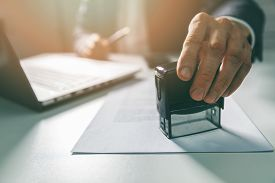 Businessman Put A Stamp On Business Contract In Office