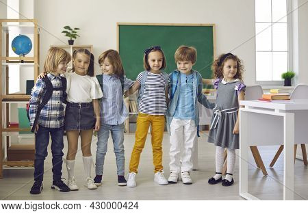 Portrait Of Happy Classmates Standing In The Class.