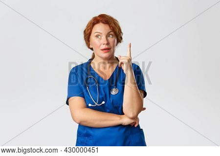 Medicine, Healthcare And Coronavirus Concept. Thoughtful Redhead Middle-aged Nurse, Doctor In Scrubs