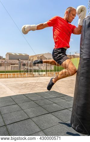 Caucasian Youong Man Hitting A Punching Bag With His Knee While Training Doing Kikcboxing. Take A Sp