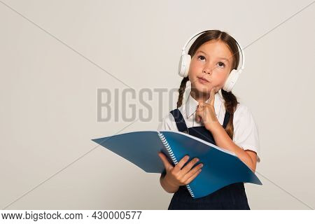 Thoughtful Schoolkid In Headphones Looking Up While Holding Notebook Isolated On Grey