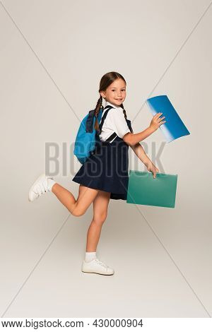 Full Length View Of Cheerful Schoolkid Running With Notebooks On Grey