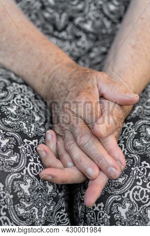 Old Woman Hands With Wrinkled Skin On Black And White With Pattern Trousers Background. Selective Fo