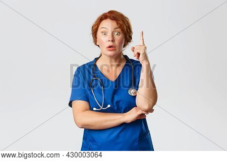 Overwhelmed Redhead Female Doctor, Middle-aged Nurse In Scrubs Have Suggestion, Saying Idea Or Plan,