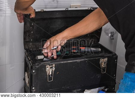 Hans Of A Man Looking For Tools In A Toolbox