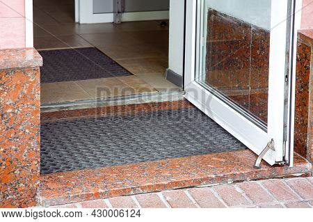 Open Plastic Entrance Doors With Glass With Rubber Foot Mat Close-up Of Building Architecture With G