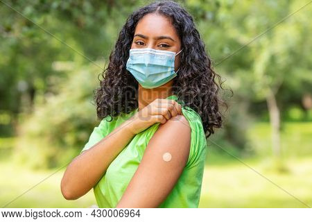 Vaccinated girl teenager teen mixed race biracial African American female young woman wearing face mask in Coronavirus COVID-19 pandemic showing vaccine band aid