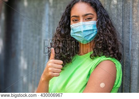 Vaccinated girl teenager teen mixed race biracial African American female young woman wearing face mask in Coronavirus COVID-19 pandemic showing vaccine band aid giving thumbs up