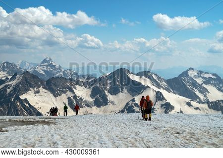 Climbers Are Walking Along A Mountain Range. A Group Of Tourists With Backpacks, Walking One After A