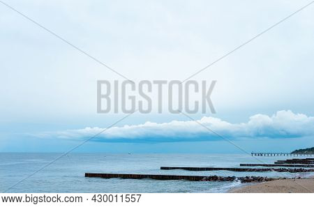 Landscape, The Blue Sky With Low Clouds Merges With The Blue Sea With Breakwaters. Can Be Used As Ba