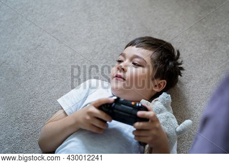 Happy Boy Lying On Carpet Holding Video Game Or Game Console. Smiling Child Playing Game Online At H