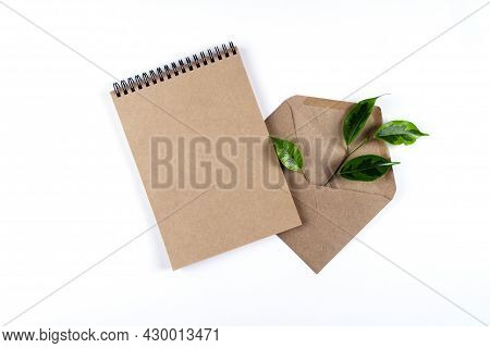 A Notepad And An Envelope Made From Recycled Paper Lie On A White Surface With A Sprig Of A Green Pl