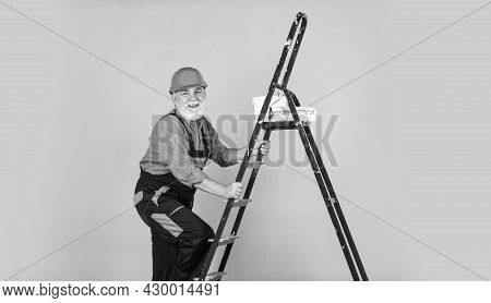 Future Profession. Senior Man Painter Use Roller On Ladder. Painting The Wall In Yellow. Professiona