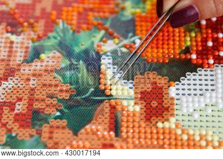 Girl Using Tweezers Takes Incorrectly Glued Acrylic Rhinestones From The Diamond Picture 3d