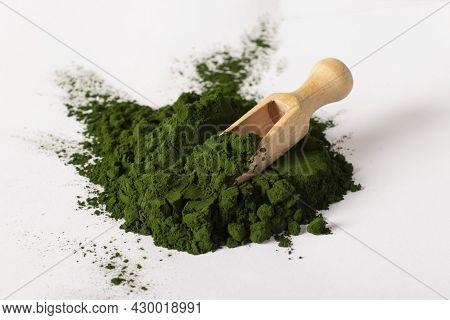 Chlorella Algae Powder With Wooden Scoop Isolated On White Background.