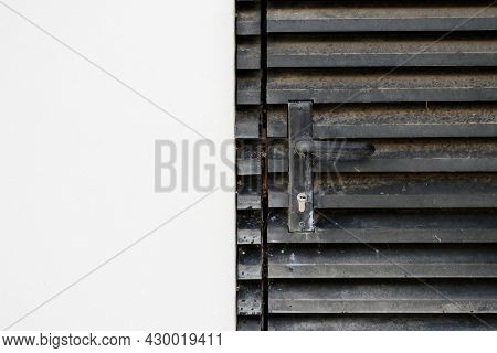 Part Of An Dirty Black Metal Door With A Doorknob And Part Of A Dirty White Wall. The Photo Is Divid
