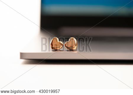 Two Tiny Golden Hearts On A Laptop. Blurred Focus. A Pair Of Lovers Met In The Office