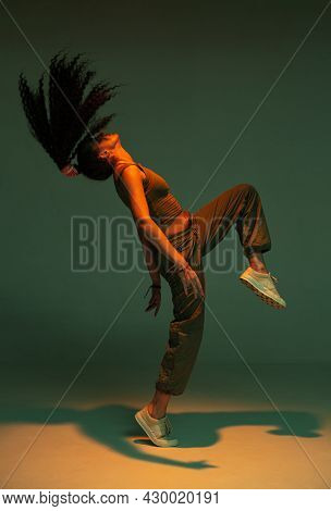 Dancing Athletic Mixed Race Girl Performing Expressive Fiery Hip Hop Or Ethnic Modern Dance In Studi