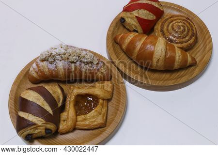 Assorted French Pastry Cake- Danish Roll, Scone, Muffin And Croissant Displayed In A Wooden Board