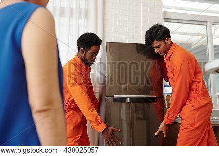 Movers In Orange Uniform Carrying New Big Refrigerator To Apartment Of Senior Woman