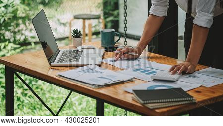 Business Woman Discussing On Stockmarket Charts In Office, Working On Laptop Computer