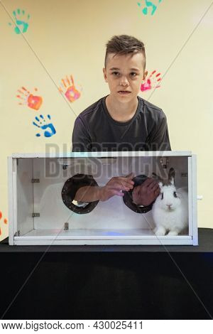 Blind guess game by touch . Young boy guesses by touch that he does not see in the box, rabbit in the box. Happy birthday celebrating or games with friends concept