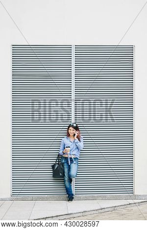 Lovely Smiling Young Woman With Cup Of Take Out Coffee Leaning On Wall And Talking On Phone