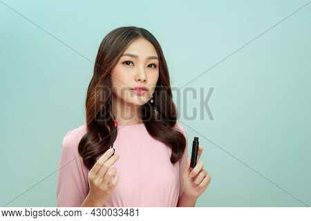 Cute Girl Applying Lip Gloss On Color Background