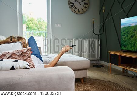 Woman Resting At Home. Person Watch Tv Set While Luying On The Sofa And Switch Channels With Remote