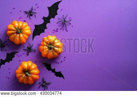 Happy Halloween Holiday Concept. Halloween Decorations, Pumpkins, Bats, Spiders On Purple Background