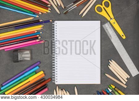 Colorful School Supplies On Blackboard. Blank Notepad With Various Pencils, Markers And Crayons. Bac