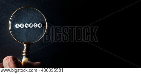 Magnifying glass on black background looking at the word search concept for searching and studying