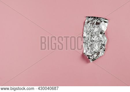 Crumpled Foil Opposite The Pink Background. Small Piece Of Aluminum Foil For Food Packaging With An