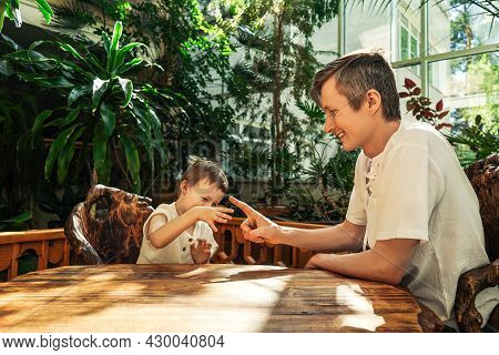 Father And Son Have Fun In Botanical Garden.