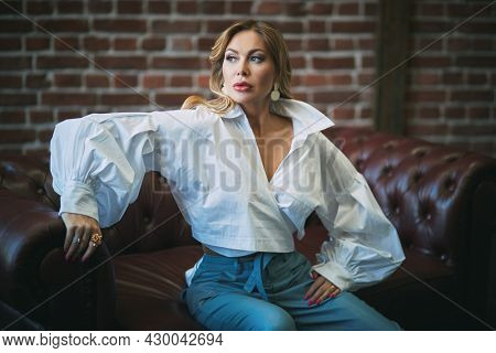 Gorgeous blonde middle-aged woman with enlarged full lips and evening makeup poses on a leather sofa. Luxury lifestyle. High fashion shot.