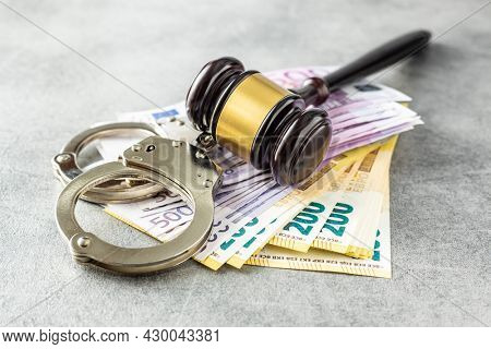 Euro banknotes, judge gavel and handcuffs on rusty table.