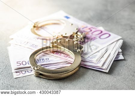 Euro banknotes and a handcuffs.