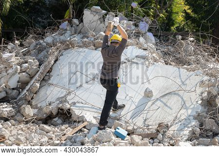 The Laborer Smashed Pieces Of The Building With A Hammer On Demolish Building. Earthquake, War, Indu