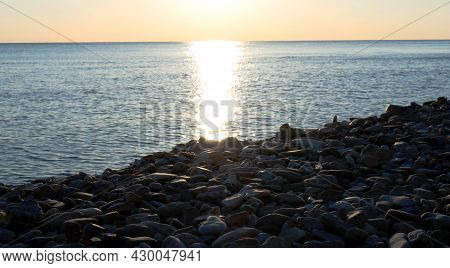 Empty Rocky Beach At Sunset With The Setting Sun And A Sunny Path On The Calm Face Of The Sea, Beaut