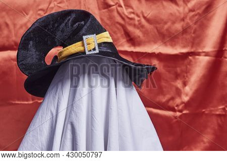 White Ghost On Orange. Halloween Holiday. A Young Child Dressed In A Ghost Costume For Halloween On