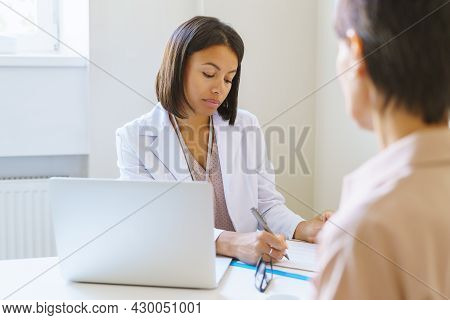 Serious Afro American Woman Doctor In White Medical Uniform Listening Female Patient, Writing Sympto