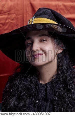 Portrait Of A Cute Multi-racial Woman In Witch Cap Against Orange Background. Studio Shot. Close-up