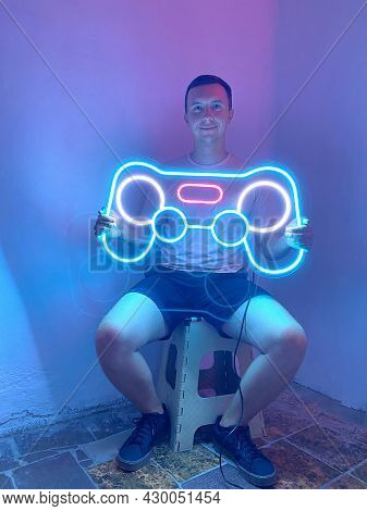 A Man Is Holding A Neon Joystick Sign In Pink, Blue And White Color. Trendy Style. Neon Sign. Custom