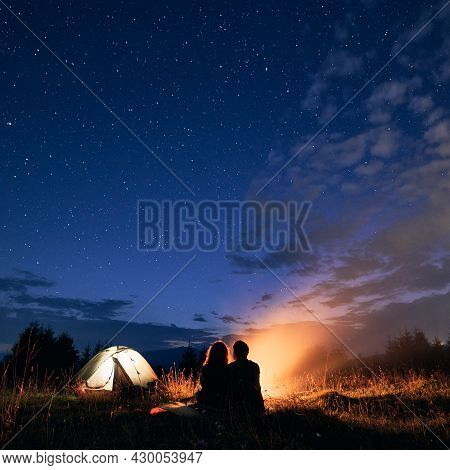 Beautiful View Of Night Starry Sky Over Grassy Hill With Illuminated Camp Tent, Campfire And Hikers.